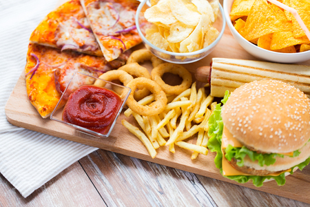 48507384 - fast food and unhealthy eating concept - close up of hamburger or cheeseburger, deep-fried squid rings, french fries, pizza and ketchup on wooden table top view