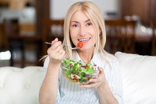 mature woman eating a healthy salad on her sofa